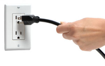 A woman unplugs an electrical cord